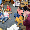 Gloucester:  Clay Pierce 3, gives David Wesson a puzzling look as he gives five fast blows into a real Skhor at the Sawyer-Free Library, for Rosh Hashanah music and story hour, Thursday afternoon. Clay also got a chance to play the Skhor,as well as his brother Jackson and sister Maia sitting with their mom at left.  Desi Smith/Gloucester Daily Times. September 22, 2011