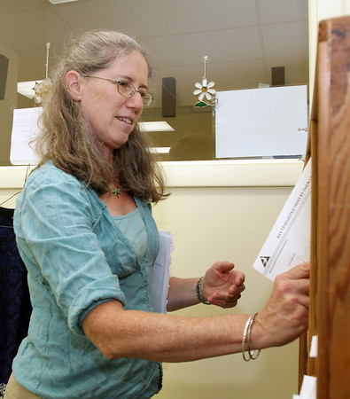 Geralyn Falco, a Conservation Agent for the Conservation Commission in Rockport organizes her new office space in the Town Hall Annex, which is located in the old Granite Savings Bank building. David Le/Gloucester Daily Times