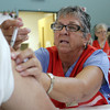 RN Grace V. Simpson, of Gloucester, gives a free flu shot to a patient at the Rose Baker Senior Center on Tuesday morning. David Le/Gloucester Daily Times
