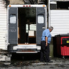 Gloucester Fire Department Captain Robert Parsons inspects some of the damage caused by the fire along the side of the building early Friday morning as cleanup began. David Le/Gloucester Daily Times