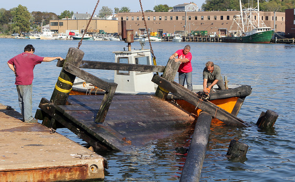 """Tom Brancelone, left, and Jack LaVie, hold the greasy pole platform as """"Tiger"""" Marston saws off the pole so it could be lifted out of the water and onto the Rose's Marina docks. David Le/Gloucester Daily Times"""