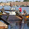 "Tom Brancelone, left, and Jack LaVie, hold the greasy pole platform as ""Tiger"" Marston saws off the pole so it could be lifted out of the water and onto the Rose's Marina docks. David Le/Gloucester Daily Times"