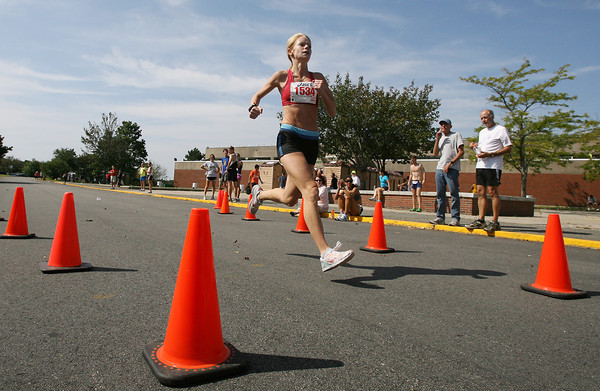 Lacy Alves, of Rockport, crosses the finish line of the Around Cape Ann 25K road race on Monday morning, taking 3rd place in the women's division. David Le/Gloucester Daily Times.