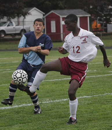 Gloucester High School's Cal Kipruto, right, flicks the ball over the head of Peabody defender Frank McMahon. David Le/Gloucester Daily Times