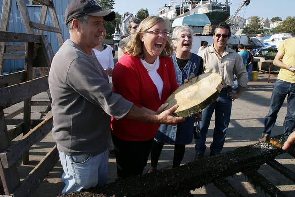 Joe Novello, President of the St Peter's Fiesta Committee and Mayor Carolyn Kirk, are handed a piece of the greasy pole platform on Friday afternoon as Katrina Turner-Rooney, and Tom Favazzo look on. David Le/Gloucester Daily Times