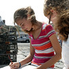David Le/Gloucester Daily Times. Sophie Palmer, 14, left, of Rockport, sits on a ledge on T-Wharf across from Motif #1 with Emily Dailey, right, also 14 of Rockport, while they paint Rockport Harbor on Friday morning