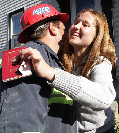 Gulnaz Urazaeva, right, hugs Action Emergency Services employee Carmine Capachietti, left, after he returned her passport from the wreckage of the Washington St. building that was destroyed by a Thursday night fire. Capachietti, along with the help of the Gloucester Fire and Police Departments recovered passports for Urazaeva and her friend Mila Zagidullina (not pictured), who will be returning to Russia next week. David Le/Gloucester Daily Times
