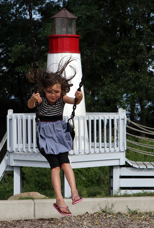 Mia Croce, 6, of Gloucester, has her hair fly in her face as she swings on the playground at Stage Fort Park. David Le/Gloucester Daily Times