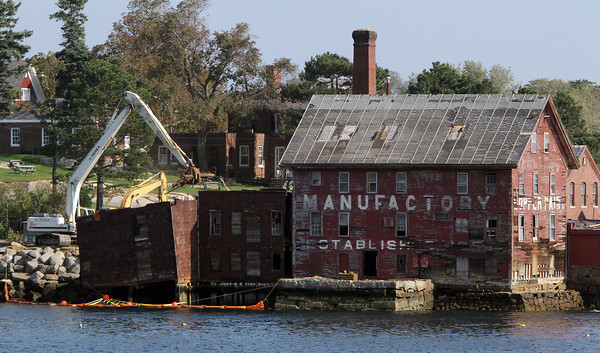 Crews started work on Tuesday afternoon to tear down the old paint factory using excavators to remove chunks of the left side of the building piece by piece. David Le/Gloucester Daily Times