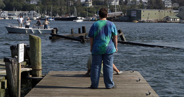 Noah McNair, 14, of Gloucester, and his mother Robyn McNair (seated in front) watch from the end of docks at Maritime Gloucester as the greasy pole platform is towed by on its way to Rose's Marina. David Le/Gloucester Daily Times