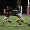 Gloucester High School senior Nick Taormina stiffarms Andover's Brendan Paquette and breaks away for a big gain on Friday evening. David Le/Gloucester Daily Times