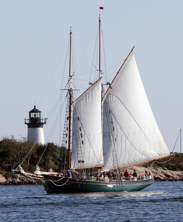The Schooner Lannan passes bye the Ten Pound Island Lighthouse on Friday afternoon on its way back to Gloucester Harbor. The Schooner Lannan will lead the Parade of Sail on Sunday morning. David Le/Gloucester Daily Times