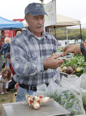 Ben Ives, of Gloucester, pays for some fresh vegetables at the Aprilla Farm stand at the Cape Ann Farmer's Market on Thursday afternoon .David Le/Gloucester Daily Times