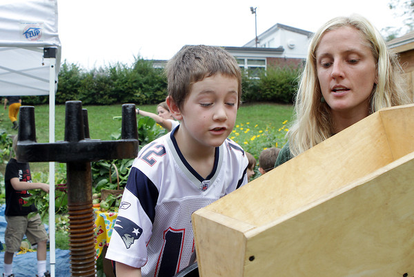 "West Parish Elementary School student Max Viera, left, looks into a chute and watches as his apple gets ground up in an apple cider press along with Alison Woitunski of the Food Project, who donated the use of the press for the school's ""Harvest Day"" on Friday. David Le/Gloucester Daily Times"