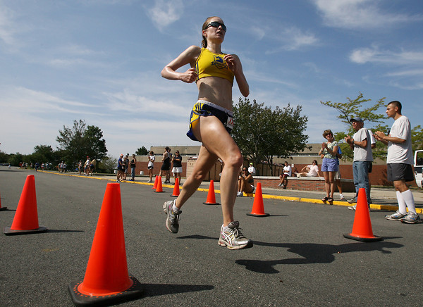 Emily Kroshus, from Boston, crosses the finish line of the Around Cape Ann 25K road race as the first woman finisher on Monday morning outside O'Maley School. David Le/Gloucester Daily Times.