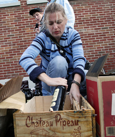 Tonya Woolcott, an employee of Savour Wine and Cheese, repackages some bottles of wine that were salvaged from the wine shop as a clean-up crew demolished the building that was decimated by a Thursday night fire. David Le/Gloucester Daily Times