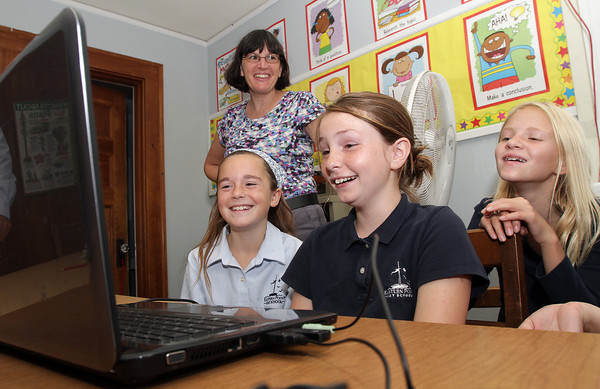 Eastern Point Day School teacher Michelle Gallo, back left, watches as Brianna Ward, 9, front left, Lainy Turner, 10, center, and Sedona Gillard, 9, laugh as they watch an educational video on Thursday afternoon.David Le/Gloucester Daily Times
