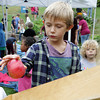 """Charlie Groleau, left, and The Food Project's Alison Woitunski, right, watch as Ian Buchanan drops an apple into an apple cider press at West Parish Elementary School's """"Harvest Day"""" on Friday morning. David Le/Gloucester Daily Times"""