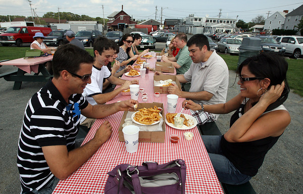 Clockwise from left, Steve Hubsch, Mario Castanheira, Kyle Hodgdon, Sarah, Jenn, Alzira, and George Castanheira, and Neil and Tara Ratna, sit out in the picnic area behind Woodman's and enjoy food they just ordered. David Le/Gloucester Daily Times.