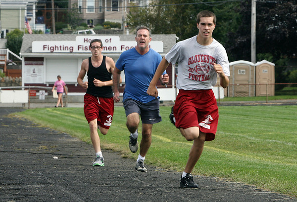 Gloucester High School sophmore Michael Sheehan, right, gym teacher John Sperry, center, and senior Travis Thans, race towards the finish of a mile run during gym class on Friday afternoon. David Le/Gloucester Daily Times.