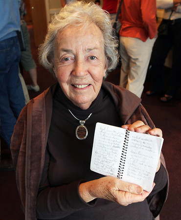 "Helen Garland, widow of ""Gloucester Icon"" Joe Garland, holds a small notepad she had found where Joe had started writing his final column that he planned to submit, shortly before he passed away. David Le/Gloucester Daily Times"
