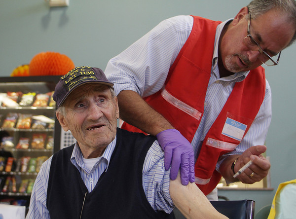 Benjamin Chiancola, left, gets his free flu vaccination at the Rose Baker Senior Center from RN Marc Reiss on Tuesday morning. David Le/Gloucester Daily Times