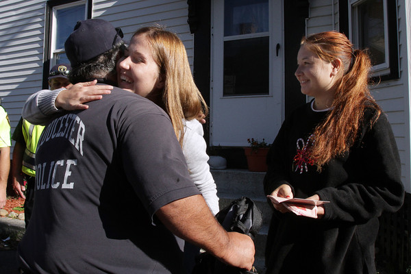 Gulnaz Urazaeva hugs Gloucester policeman Mark Foote after he, combined with firemen and a few members of Action Emergency Services, rescued passports from the fire wreckage for her and her friend Mila Zagidullina, right. David Le/Gloucester Daily Times