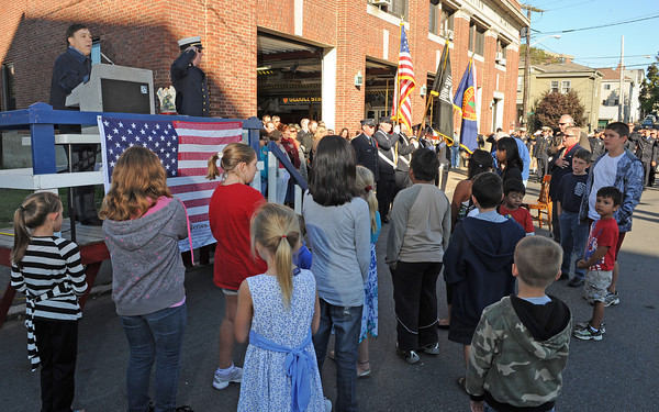 Gloucester: John Nicastro leads a group of young children and adults in God Bless America, remembering the 10th year of 911 in a ceremony held at Central Fire Station Sunday morning.   Desi Smith/Gloucester Daily Times. September 11, 2011