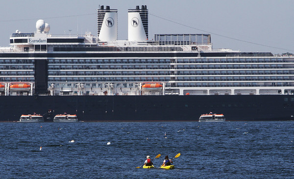 Two kayakers paddle out to get a closer look at the Eurodam cruise ship which docked at the mouth of Gloucester Harbor on Monday. David Le/Gloucester Daily Times