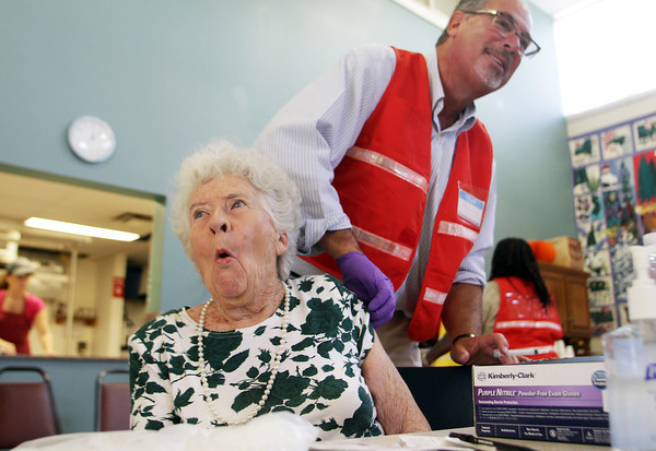 Patricia Ireland, of Gloucester, reacts after getting a flu shot from RN Marc Reiss, also of Gloucester, at the Rose Bake Senior Center on Tuesday morning. David Le/Gloucester Daily Times