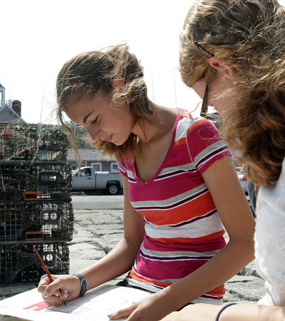 David Le/Gloucester Daily Times. Sophie Palmer, 14, left, of Rockport, sits on a ledge on T-Wharf across from Motif #1 with Emily Dailey, right, also 14 of Rockport, while they paint Rockport Harbor on Thursday morning.