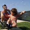 Ajay Dort, 1, sits with his mother Jaime Dort, at the Fort Park on Tuesday afternoon and plays with a bubble wand. David Le/Gloucester Daily Times