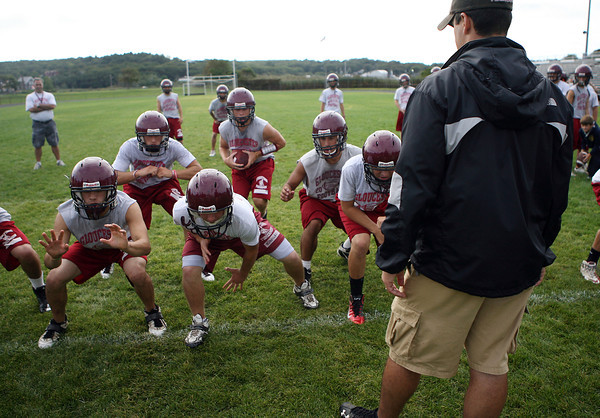 New Gloucester High School Football coach Tony Zerilli, right, looks on as his team practices on Thursday afternoon in preparation for their first game on Friday evening against Lynn Classical. David Le/Gloucester Daily Times.