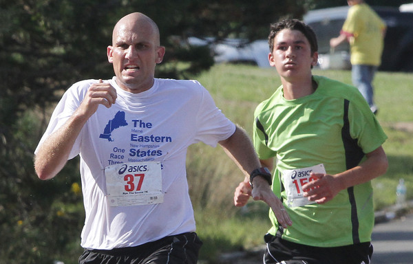 Sean Kay, left, of Revere, holds off Matthew Ciaramitaro, of Gloucester  in the last hundred yards of the Run the Goose 7K road race on Monday morning. David Le/Gloucester Daily Times.