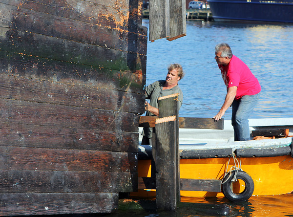 """""""Tiger"""" Marston, left, and Jack LaVie, work to saw off pieces of the greasy pole platform in order to lift it out of the water and onto the docks at Rose's Marina on Friday afternoon. David Le/Gloucester Daily Times"""