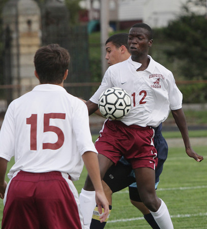 Gloucester's Calvin Kipruto (12) shields the ball from a Peabody defender and looks to pass to teammate Alex Dahlmor (15). David Le/Gloucester Daily Times