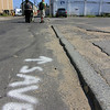 Allegra Boverman/Gloucester Daily Times Granite curbing along Commercial Street in Gloucester. It was hand-cut from Cape Ann granite and dates back to the 1800s. Don Peavey, the public works inspector for the City of Gloucester, shows where he would mark the pavement to save the hand-cut granite curbing, and also marked other places on the pavement where utlities are located such as gas and water lines, other dig safe markings, and sewer manhole covers to remove and replace once the street and sidewalks are redone, should a new hotel be built on the site of the Birdseye Building on Commercial Street in Gloucester.