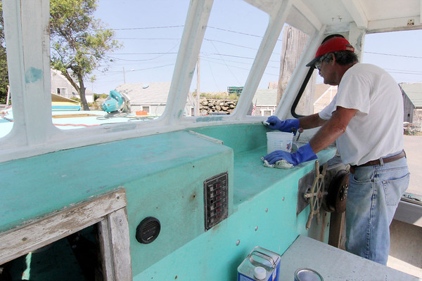 Allegra Boverman/Gloucester Daily Times. Jimmy Fritz of Rockport scrubs his lobster boat at the Pigeon Cove Boat Owners Association Boat Wash on Wednesday. He also washed it there and is doing various repairs and maintenance while it's up out of the water.