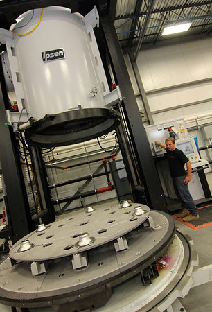 Allegra Boverman/Gloucester Daily Times. BOMCO special process and heat treating engineer Alex Muenzner, of Gloucester, shows how a vacuum furnace works at the company on Tuesday. The machine can harden or soften metal parts according to their needs.