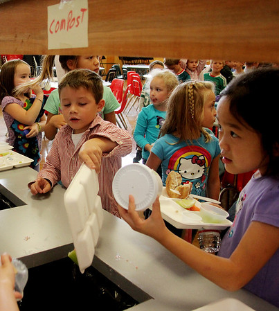 Allegra Boverman/Gloucester Daily Times. Dex Woodman, left, and Joanna Shan, right, both Essex Elementary School first graders, recycle and compost the remains of their lunch on Friday at the school.