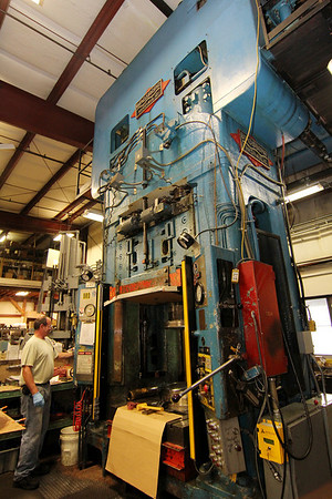 Allegra Boverman/Gloucester Daily Times. BOMCO press operator Chris Crivello works with a hydraulic press to make non-moving engine parts at the company. This press applied 750 tons of pressure to metal for casings and housings.