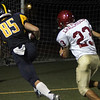 Allegra Boverman/Gloucester Daily Times. Andover: Andover's Will Heikkinen, left, scores a touchdown while chased by  Gloucester's Carlo Cracchiolo, right during their game in Andover on Friday night.
