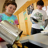 Allegra Boverman/Gloucester Daily Times. Essex Elementary School fifth graders Tim Reilly, left, and Jes MacDonald are part of the school's Green Team. It's their job to empty and put new bags into the wall-mounted composting buckets that are positioned in all the hallways at the school.