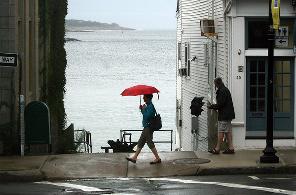 ALLEGRA BOVERMAN/Gloucester Daily Times  To open or close an umbrella on Tuesday along Main Street in Rockport? It was raining on and off in the area and there will be showers on Wednesday.
