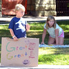Manchester:   Charlie Swanson 6, waves at cars while holding his sign hoping to bring in some business, as his sister Paige 10, organizes their books on the lawn next to the Town Hall Monday afternoon.  Desi Smith/Gloucester Daily Times. September 3, 2012