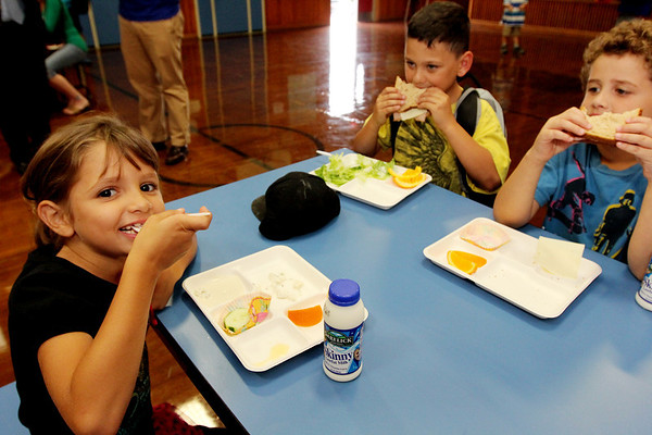 Allegra Boverman/Gloucester Daily Times The Super Snack program kicked off at Veterans Memorial Elementary School on Monday afternoon in conjunction with the Passport to Fitness Program which also kicked off at the same time. Children at the school can get a wholesome, hearty snack that could double as a meal if needed, after school from 3-3:30 p.m. Monday through Thursday. It is staffed by Open Door Food Pantry staff. They can also participate in the Passport to Fitness program which is staffed by Cape Ann YMCA staff. There will also be crafts, games and time to do work in the school's vegetable garden. Harvard Pilgrim Healthcare Foundation members were on hand to give a $10,000 check to help fund the program, which is a collaboration with the school, the city, Cape Ann YMCA, the Open Door Food Pantry, Addison Gilbert Hospital and the Food Project. From left, enjoying their Super Snack on Monday after school are second graders Chloe Aiello, Cam Mickels and Joseph Miranda.