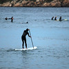Jim Vaiknoras/Gloucester Daily Times: <br /> A stand up paddle boarder heads out to the surf on Good Harbor Beach as a large group of surfers wait for a wave Tuesday night.