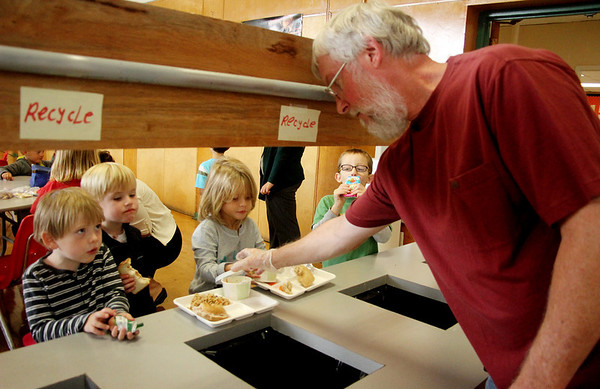 Allegra Boverman/Gloucester Daily Times. Essex Elementary School head custodian Rob Page, right, helps kindergarteners and first graders with the proper disposal of their lunches on Friday at the school. The school composts and recycles their trash. From left are kindergarteners Bjorn Arnason, Chase Koeplin, Chloe Baker and first grader George Mullin.