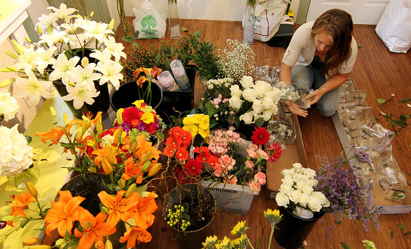 Allegra Boverman/Gloucester Daily Times Elise Jillson of West Gloucestre arranges finished corsages for a wedding that Celia Gibson of Celia's Flower Studio was preparing on Friday at the Lanesville shop.