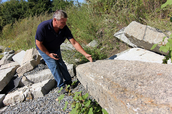 Allegra Boverman/Gloucester Daily Times. Don Peavey, the public works inspector from Gloucester, talks about these large pieces of Gloucester granite curbing that they save and reuse when they are working on streets in Gloucester.